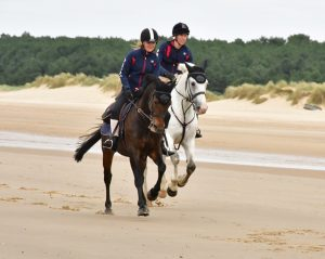 Georgie and Edward ride into Holkham beach CREDIT Veale Family 300x239 - Over £13,000 raised for St Elizabeth Hospice after 200-mile coastal horse ride in memory of much-loved father